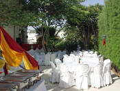 A garden venue with the tables and chairs ready but before decoration