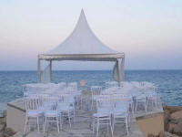 Beach wedding marquee with chairs at sunset for hire