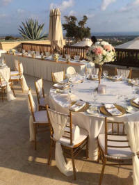 Table settings and chairs in an open area or balcony